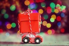 运载在五颜六色的bokeh背景的微型红色汽车一个大红色箱子 假日圣诞快乐概念 免版税库存照片