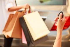 运载在停车场概念的女性夫人五颜六色的购物袋 使用遥控的夫人手发出信号开锁 免版税库存图片