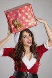 运载在她的头的年轻圣诞老人帮手女孩大当前包裹 免版税图库摄影