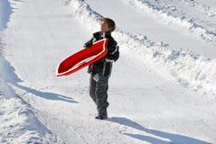 运载在小山下他的雪撬的男孩 免版税库存照片