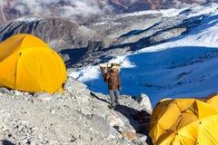 运载在山远征阵营的尼泊尔夏尔巴搬运工柳条筐 免版税库存图片