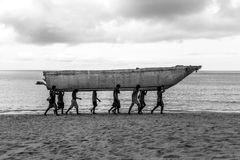 运载在泰国海滩的男孩一条小船 免版税库存图片
