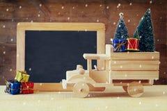 运载在黑板前面的木汽车一棵圣诞树 免版税库存照片
