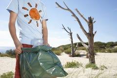 运载塑料袋的男孩充满在海滩的垃圾 免版税库存图片