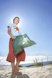 运载塑料袋的男孩充满在海滩的垃圾 库存图片