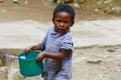 运载塑料水桶的可怜的马达加斯加人的男孩 免版税库存图片