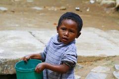 运载塑料水桶的可怜的马达加斯加人的男孩 库存照片