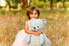 运载填充动物玩偶的领域的两岁的女孩 免版税库存照片