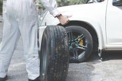 运载备用轮胎的白色制服的汽车技工人准备变动汽车轮子  汽车修理服务 图库摄影