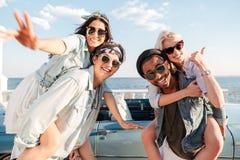 运载女孩和显示赞许的两个人在夏天 免版税图库摄影
