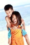 运载她的兄弟的愉快的小女孩 免版税库存图片