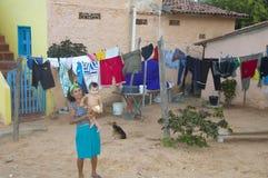 运载她的在她的房子前面的妇女婴孩 免版税库存图片