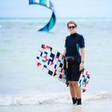 运载她的委员会的女性kiteboarder 免版税库存图片