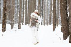 运载她的婴孩的年轻母亲在森林里在多雪的天 库存照片