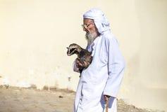 运载小山羊的老人在Sinaw市场上 库存图片