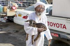运载小山羊的老人在Sinaw市场上 库存照片