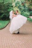 运载微笑的新娘的愉快的新郎的敏感照片在公园 免版税库存照片
