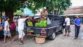 运载新鲜水果的人们对市场在巴厘岛,印度尼西亚 图库摄影