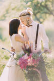 运载有桃红色花花束的可爱的新婚佳偶的特写镜头垂直的照片自行车在 免版税库存照片