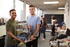 运载机器或设计类的两位男性大学生画象在科学机器人学方面 库存照片