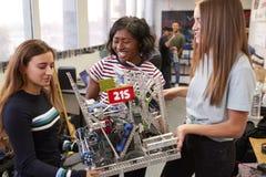 运载机器或设计类的女生大学学生在科学机器人学方面 库存图片