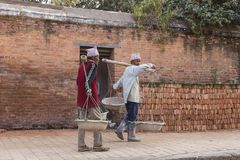 运载材料的尼泊尔工作者修理地震损坏了世袭财产大厦 库存照片