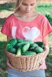 运载柳条筐用黄瓜的女孩 免版税库存照片