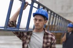 运载梯子的建筑工人 图库摄影