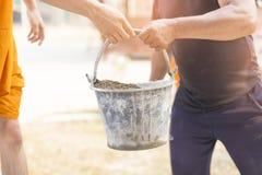 运载混合的建筑沙子与水泥和修建房子的更老的劳方或工作者 库存照片