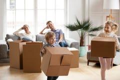 运载箱子的逗人喜爱的小孩子一起使用在移动的天 库存图片