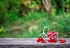 运载红色木心脏的白色玩具自行车 红色木心脏在木地板上落 心形的玩具转达对情人节 库存照片
