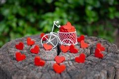 运载红色木心脏的白色玩具自行车 红色木心脏在木地板上落 心形的玩具转达对情人节 免版税库存图片