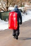 运载红色长橇的男孩 免版税库存照片