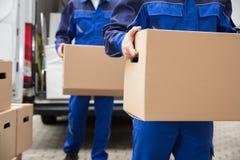 运载纸板箱的两名搬家工人特写镜头  免版税库存照片