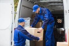 运载纸板箱的两名搬家工人 库存照片