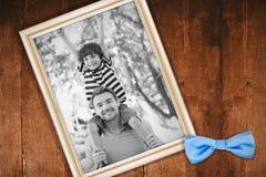 运载肩膀的父亲的综合图象一个愉快的儿子在公园 免版税库存照片