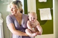 运载胖的逗人喜爱的母亲的婴孩 免版税图库摄影