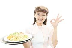 运载膳食的微笑的女服务员 库存照片
