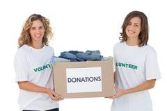 运载衣裳捐赠箱子的两个快乐的志愿者 免版税库存照片
