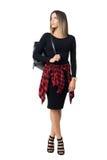 运载袋子的高跟鞋的时髦的女孩回顾在肩膀 免版税库存照片