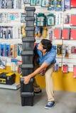 运载被堆积的重的工具箱的人在商店 免版税库存照片