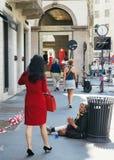 运载豪华物品袋的妇女通过叫化子通过Montenapoleone在米兰,意大利的豪华中心 免版税库存图片