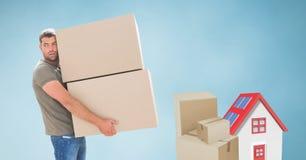 运载重的小包的送货人由房子 免版税图库摄影