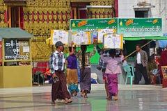 运载重的箱子的一个小组勤勉缅甸妇女和人在他们的头顶部 免版税图库摄影