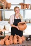 运载陶瓷船的高兴的妇女陶瓷工 免版税库存照片