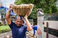 运载水泥的分数的被倾销的卡车的未知的名字工作者 免版税库存照片