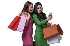 运载购物袋的两个亚裔女性朋友,当看时 免版税库存图片