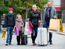 运载购物袋的游人家庭  免版税库存照片