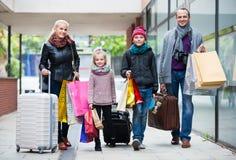 运载购物袋的游人家庭  库存照片
