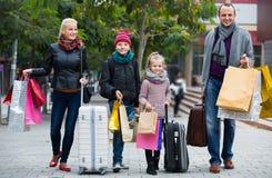 运载购物袋的游人家庭  免版税图库摄影